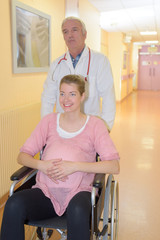 pregnant woman in wheelchair with doctor in the hospital corridor