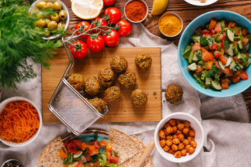 Fresh fried falafel balls on wooden board surrounded with different ingredients
