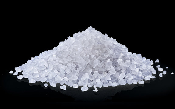 heap of salt isolated on black background.