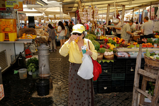 A woman drinks an orange juice in downtown Rome