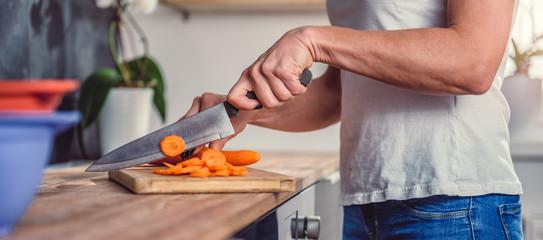 Woman cutting carrot