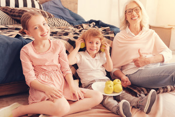 Radiant lifestyle. Funny grandchildren and their emotional grandmother sitting on the floor and making faces while posing with a plate full of ripe apples.