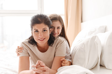 Image of happy adult woman 30s with little girl 8-10 lying on bed in bedroom at home, and looking at camera