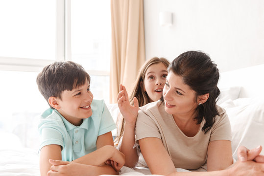 Image of happy family woman 30s with little kids 8-10 lying on bed in bedroom at home, and having fun