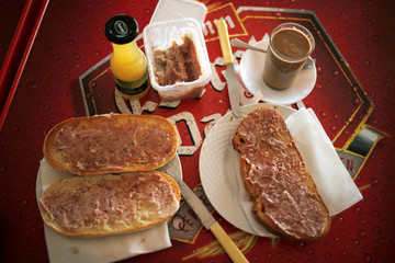 """Traditional bread for breakfast named """"mollete"""" and """"toast"""" spread with """"zurrapa"""" (fried loin of pork in butter and salt) are seen on a table with coffee and pineapple juice during a breakfast at """"El Navasillo"""" restaurant in Parauta"""
