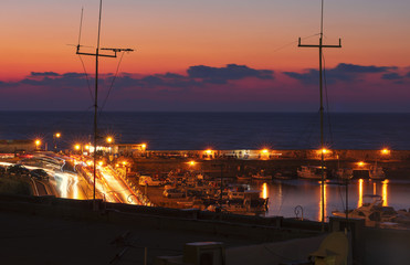 Night embankment and bay in Heraklion with night illumination and sunset (Greece)