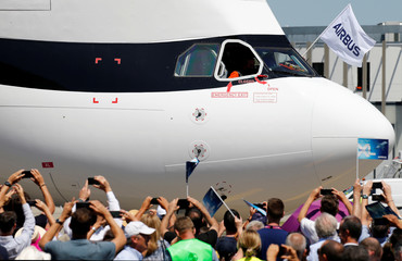 People take pictures as an Airbus Beluga XL transport plane lands during its first flight event in Colomiers near Toulouse