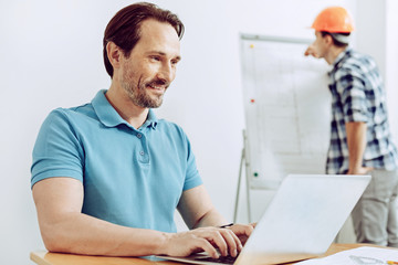 Smart man. Calm positive clever man working on a laptop while his colleague standing behind his back