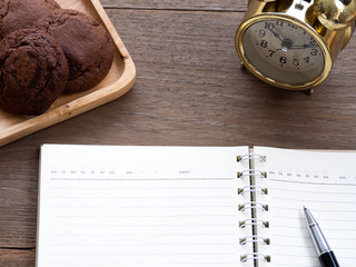 The open blank notebook side of the cookie and there is a golden clock in the side on the wooden table.