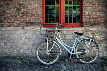 Bicycle with basket in fromt of old wall with red window