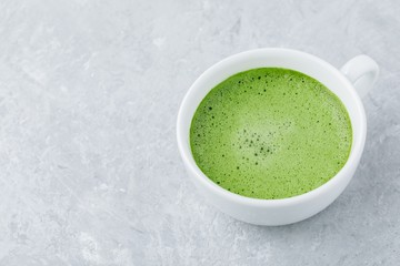 Japanese matcha green tea latte in white cup on gray background