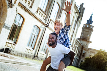 Joyful mood. Strong African student showing his teeth and looking forward while running in the yard with his partner