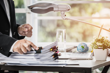 Businessman hands holding pen for working in Stacks of paper files searching information business report papers and piles of unfinished documents achieves on laptop computer desk in modern office