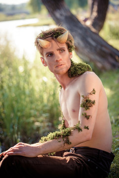 The Forest King. king of beasts in fur. wild young man. horns and makeup. fashion concept to chelowin. river forest and sun
