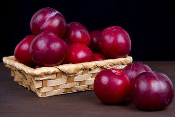 ripe plum in a basket on a wooden table dark background