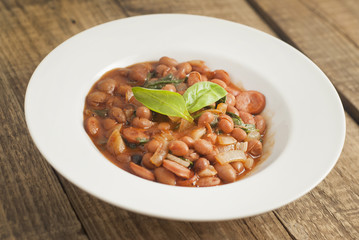Cooked Red Beans in Tomato Sauce with Spinach and Onion, white Round Plate, Wooden Background, Top view.