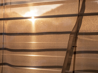 sun shining through roller blinds and curtain