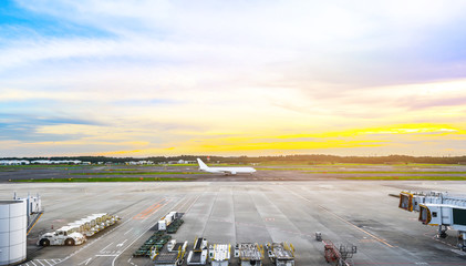 Business & travel concept : panoramic view of apron and airplane on runway under dramatic sunset & cloud sky
