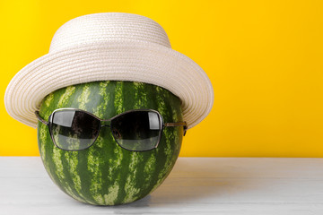 A large watermelon in sunglasses and a summer hat on a bright yellow background
