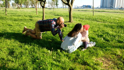 Young father photographing kissing mother and daughter in the park at sunset. Happy family taking photos in nature