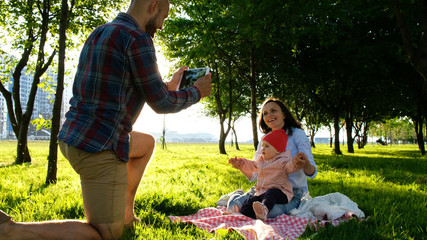 Happy family is laying on the pled and doing selfie with a baby at sunset in the park. Father takes pictures of themselves with the baby on a tablet