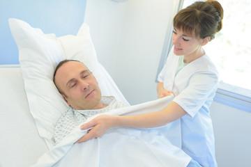 nurse talking care patient bed hospital