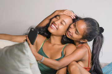 young happy beautiful Asian sisters or girlfriends couple smilin
