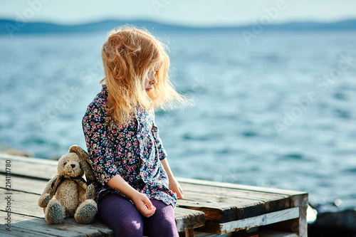 A little sad girl with a plush Bunny sitting on a wooden bridge