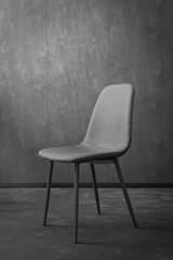Grey modern textile chair with wood on a background of a wall.