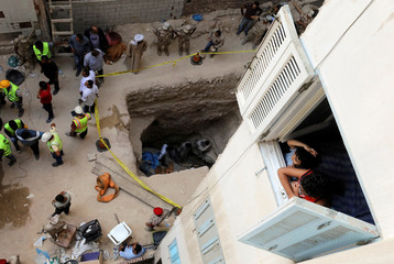 Children and residents watch archaeologists unearth coffin containing three mummies with sewage water and bones inside in Alexandria