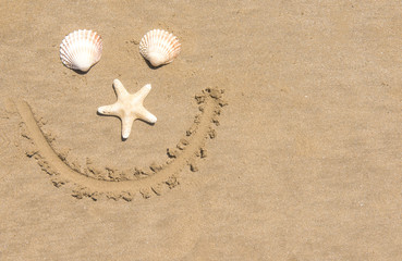 Smiling face drawn into the sand on a beach