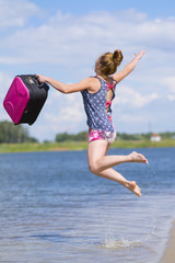 Happy girl jumps into the pond with a suitcase in his hands