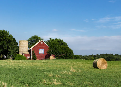 Bright red barn with barn quilt and silo against a bright blue summer sky. Large round hay bales are in the field in front of the barn. Concepts of family farm, farming, agriculture, harvest, summer