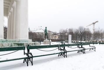 winterlicher Volksgarten in Wien mit Blick auf den Theseustempel, Skulptur und Baukran vor mit Schneebedeckten Parkbänken