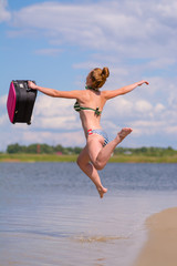 Joyful girl jumps into the sea with a suitcase in a swimsuit.
