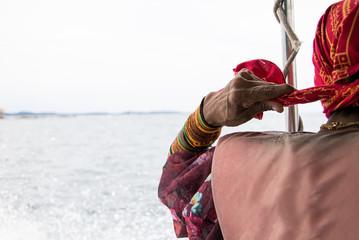 indigenous woman wearing lifejacket tying head gear on water