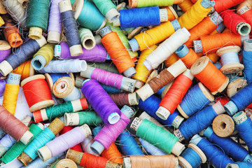 Heap of multicolored sewing threads in spools taken as background.