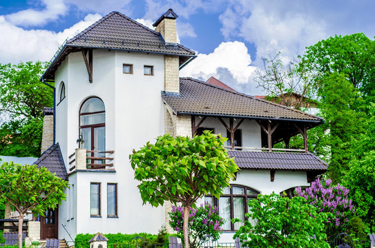 House Mediterranean style, green trees and lilac bushes in front of