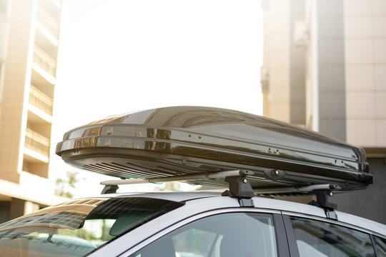 long black trunk on the roof of a white car. Travel and accessories for transportation.