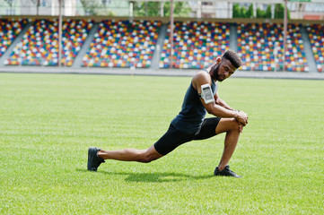 African american male athlete in sportswear doing stretching exercise at stadium.
