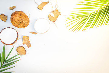 Summer flat lay scene with palm leaf and coconut fruits on wooden background, retro toned