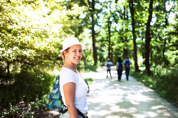 Beautiful woman smiling at path in a forest during hiking with friend