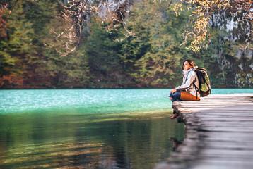 Woman traveler sits on wood bridge on mountain lake at sunny autumn day