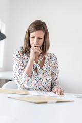 Woman sitting at her desk in the office analyzing business documents or plans