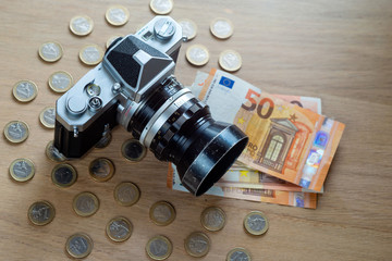 Euro banknotes, coins and a camera on a light wooden background.