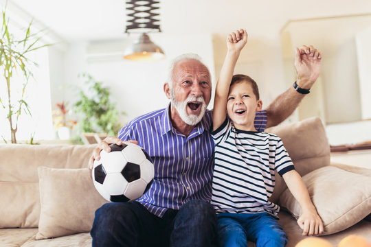 Little boy on couch with grandfather cheering for a football game