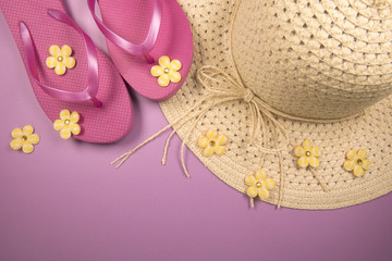 Background image of a sun hat and pink flip flops on a pink background with copy space
