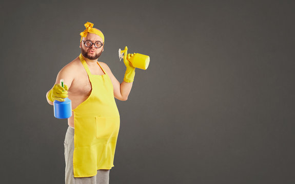 Funny fat cleaning man in an apron on cleaning on a background for text.
