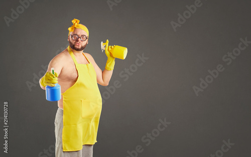 Funny fat cleaning man in an apron on cleaning on a