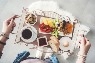 Delicious breakfast on tray carried by a young woman